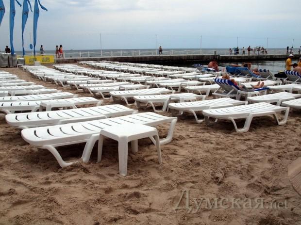 Весь пляж полностью заставлен топчанами-шезлонгами