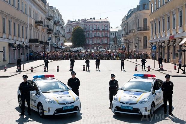 Присягу новой полиции охраняли старые милиционеры (между машинами и народом)